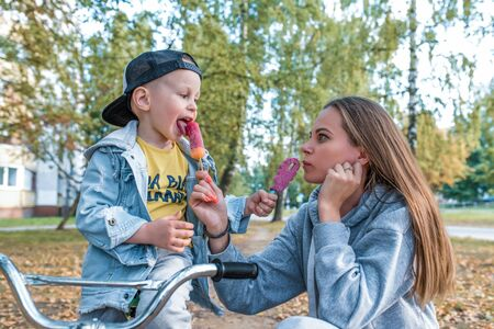 Family mother woman little boy son 3-5 years old, summer city autumn, eat vanilla ice cream, play fun, emotions relaxation weekend. Casual clothes, parenting support care love child