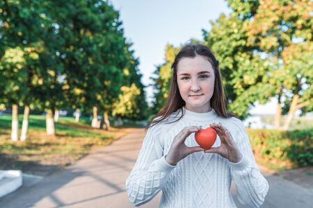 Teenager girl 12-15 years old, autumn day summer in city, in hands toy red heart, concept of help and blood donation, give love, care and new life, Valentines Day. Free space for text.