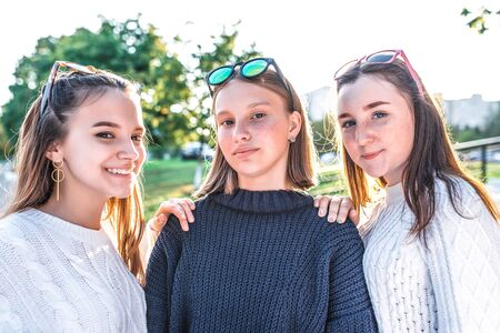 Three girls schoolgirls teenagers 13-15 years old, posing for photograph. Emotions of joy, fun enjoyment, happy smiling, casual sweater clothes, relaxing after school on vacation
