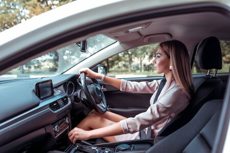 Beautiful girl business lady, summer city, rides car interior. Tanned skin, formal suit long hair casual makeup. Car rental, car sharing. Right-hand drive, left-hand drive, automatic transmission