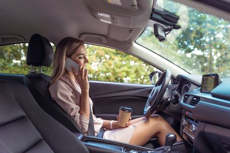Beautiful girl business lady summer city car. Talking phone happy smiling standing traffic jam parking lot snacking cup coffee tea. Car rental, car sharing. Automatic transmission. Autumn day nature