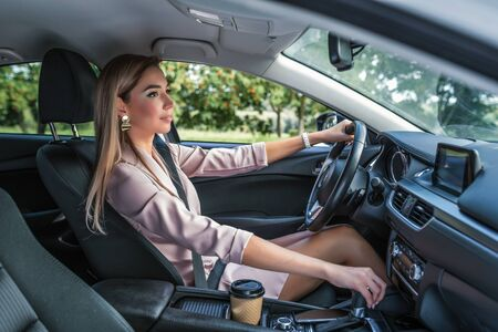 Beautiful girl business lady summer city car. Reversing, looking mirror, engaging reverse gear, standing traffic jam parking lot. Car rental, car sharing. Automatic transmission. Autumn day nature. Stok Fotoğraf
