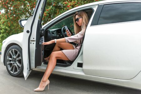 Beautiful girl business lady, summer autumn city, gets out car, getting car tanned leather shoes. Car rental, car sharing. Car parking, business meeting city. Mobile phone, call reads writes message