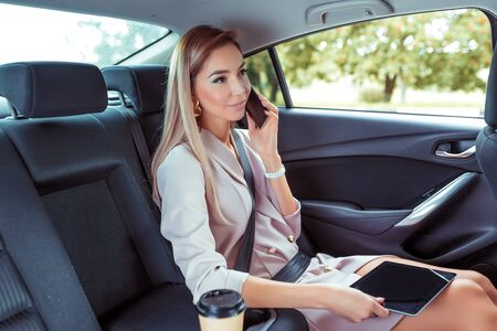 Beautiful woman car interior passenger, phoning, working road, tablet touch screen. Business VIP taxi rental car sharing city. Summer girl autumn city. Strict suit, long hair casual makeup