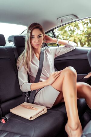 Beautiful girl business lady, summer autumn city, in car, straightens her hair. Strict suit tanned skin long hair casual makeup. Car rental, car sharing. Car parking, business meeting in city Stok Fotoğraf