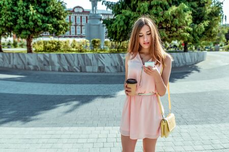 girl in pink dress, stands in city in summer, looks at phone, reads a message online on Internet, a cup of coffee tea, social networking application. Free space for text Stok Fotoğraf