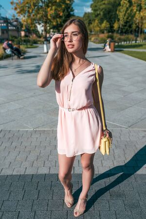 Beautiful girl in pink dress, corrects glasses, in summer in city, fashionable and modern fashion lifestyle. Handbag over shoulder, tanned figure. Stok Fotoğraf