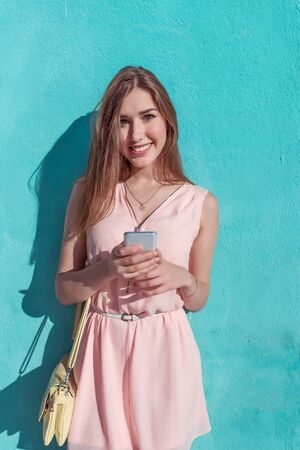 Beautiful girl in pink dress, happy smiles in her hands a telephone, in summer in city, fashionable and modern fashion lifestyle. Handbag over the shoulder, tanned figure