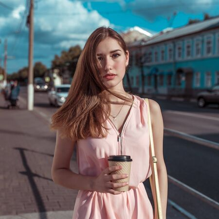 Beautiful girl pink dress, background road buildings in hands of cup with coffee tea, in summer in city, fashionable and modern fashion lifestyle, tanned figure.