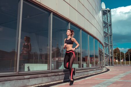 Young athletic woman running in summer on jogging in city, background glass windows of building, sportswear. Athletics training, day morning. Active fitness lifestyle, free space text motivation
