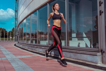 woman running young athletic in summer on jogging in city, background glass windows of building, sportswear. Athletics training, day morning. Active fitness lifestyle, free space text motivation