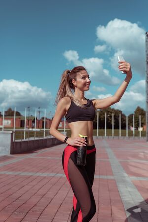 Girl athlete happy taking pictures herself on phone, relaxing after workout, in summer day city. Enjoys video call application on Internet. Active lifestyle fitness, fashionable and stylish woman