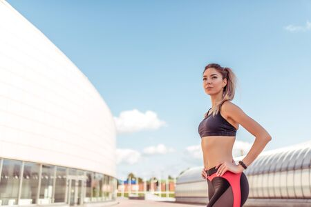 Young and athletic woman standing in city on summer, background building, sportswear. Athletics training, day morning. Active fitness lifestyle, free space for text motivation