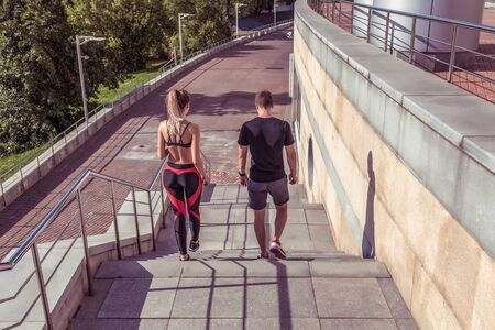 Young athletic couple man woman, walk on stairs, in summer jogging city, view from back, sportswear. Athletics training, day morning. Active fitness lifestyle, free space text motivation Stok Fotoğraf