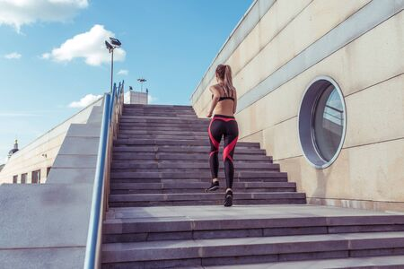 Young athletic woman running on stairs, in summer on jogging in city, view from back, sportswear. Workout athletics, day morning. Active fitness lifestyle, free space for text motivation