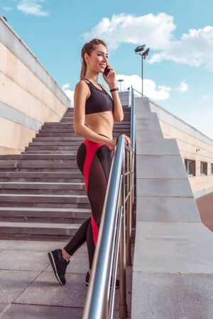 Girl athlete stands happy talking phone, resting after training, summer day in city. Enjoys walk, listens to message on Internet application. Active lifestyle fitness, fashionable stylish woman