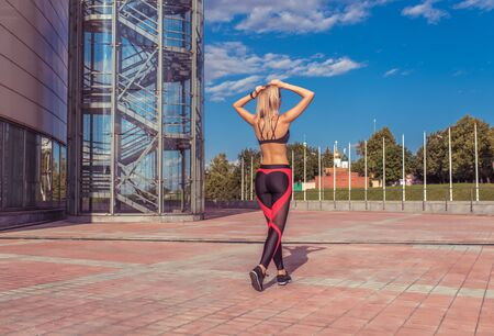 Girl athlete walks training, rest after jogging, summer day city. Enjoys walk. Active lifestyle fitness fashionable stylish woman. View from back, Free space motivation text. Sportswear tanned figure Stok Fotoğraf