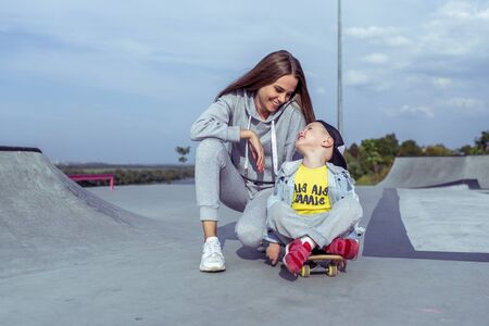 Happy family mother woman little boy son 3-5 years old, summer sports field city, playing skateboarding, emotions joy, fun relaxation weekend. Everyday clothes, parenting support care child