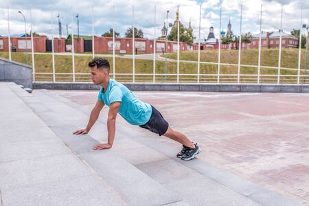 Male athlete doing push-ups and training abdominal muscles plank workout, summer in city. Fitness motivation youth lifestyle. Free space for copy text Stok Fotoğraf