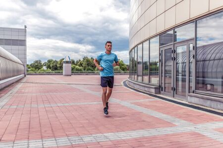 male athlete runs in morning on run, in motion, workout training, in summer in city. Fitness motivation youth lifestyle. Free space for copy text.