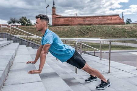 male athlete, push-ups, lying down, workout training, chest muscles, summer in city. Fitness motivation youth lifestyle. Sportswear, shorts and T-shirt in sneakers. Cloud stair background. Stok Fotoğraf