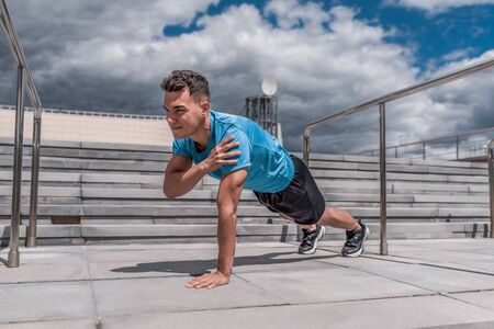 Male athlete training abdominal muscle press, workout training, summer in city. Fitness motivation youth lifestyle. Sportswear, shorts and T-shirt in sneakers. Cloud stair background.