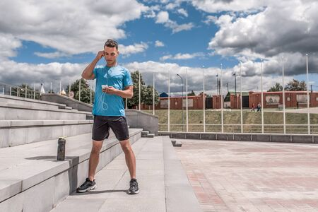 male athlete listens to music in headphone in hand smartphone, workout , in summer city. Fitness motivation youth lifestyle. Sportswear, shorts and T-shirt in sneakers. Free space for copy text