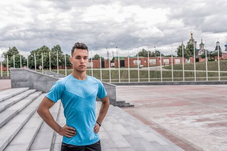 male athlete posing and looking confidently, coach controls in summer in city. Fitness motivation youth lifestyle. Free space for copy text. Background stairs, clouds Stok Fotoğraf