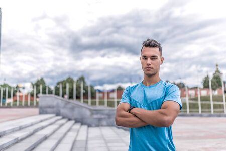 male athlete posing and looking confidently, coach controls in summer city. Fitness motivation youth lifestyle. Free space for copy text. Background stairs, clouds. Sportswear T-shirt