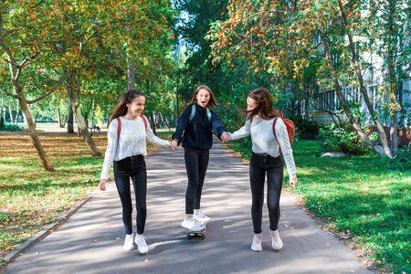 Girls teenage schoolgirls ride skateboard after school, happy smiling, emotions of joy, delight and fun, warm sweaters in autumn on street in city. Best friends girlfriends.