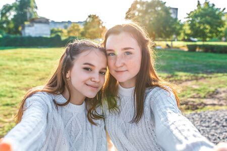 Two girls schoolgirls girlfriends 13-15 years old, take selfie on phone in summer in city after school happy smiling. Casual wear knitted sweater. Autumn, lawn trees background. Stok Fotoğraf