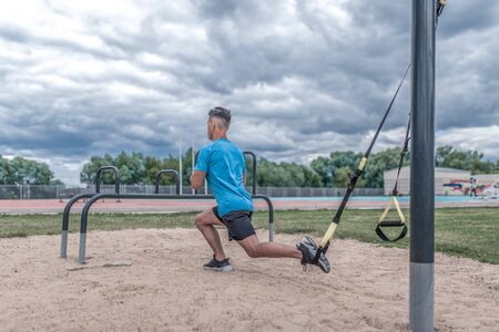 Young sportsman, male athlete, makes lunges with straps, loops for training legs, summer day city, fitness workout, active lifestyle modern youth, sportswear. Motivation life. Free space copy text Stok Fotoğraf