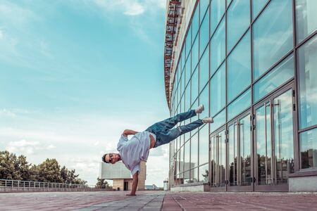 Strong man acrobat dancer, handstand, breakdance dancing, summer city, free space text, hip hop dancer. Youth lifestyle, active, trend modern, fitness sport, motivation