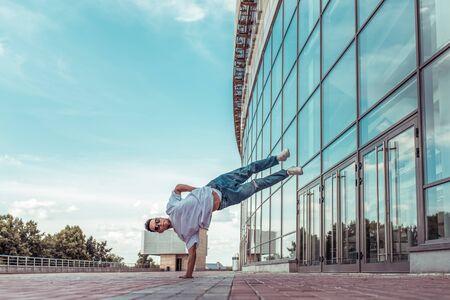 Strong man acrobat dancer, handstand, breakdance dancing, summer city, free space text, hip hop dancer. Youth lifestyle, active, trend modern, fitness sport, motivation