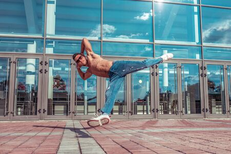 Man dancer, muscle jump in flight, dancing breakdance, summer in city, free space for text, hip-hop break dancer. Youth lifestyle, active, trend modern, fitness sport, positive motivation