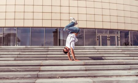 man dancer, stand on upside down, dancing breakdance, summer city, free space for text, hip hop dancer. Youth lifestyle, trend modern, fitness sport, positive motivation