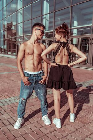 cheerful couple man and girl, laughing, dancers trained and tanned torso, dance sport, summer in city, hip hop, dance style, youth lifestyle. Street urban fitness motivation 写真素材