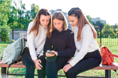 3 girls girlfriends teenagers 13-15 years old, sit bench autumn afternoon park relax after classes college school, watch videos social networks smartphone screen. In casual wear, sweater and jeans. Stockfoto