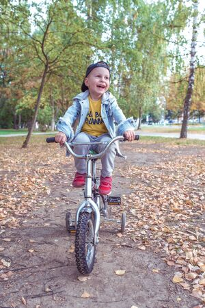 Little boy 3-5 years old, learning to ride bike, autumn day, casual warm clothes. Denim with baseball cap. Driving lessons, first experience, sports in park. Happy smiles laughs and rejoices, has fun