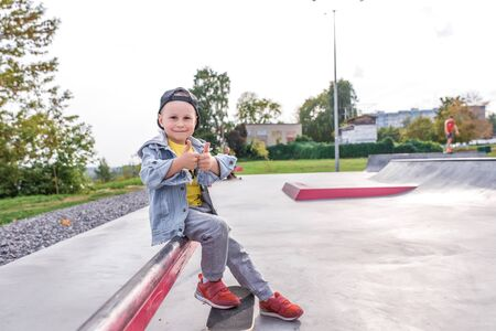 Little boy 3-5 years old, learning to ride skateboard, autumn day, casual warm clothes. Denim with baseball cap. Driving lessons, first experience, outdoor sports. Free space for copy text.