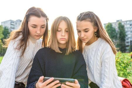 Three girls schoolgirls teenagers 13-15 years old, fall day summer city watch videos smartphone, online application social networks Internet.