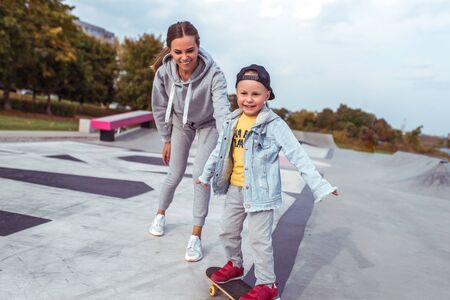 Young family little boy 3-5 years old, woman mother, happy smiling, learning to ride a skateboard, in the summer in a city park. Weekend rest on sports field. Skateboard casual wear