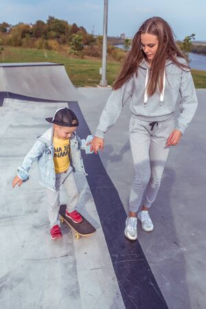 Young family little boy 3-5 years old, mother woman, study and train, learn to ride a skateboard, in the summer in a city park. Weekend rest on sports field. Skateboard casual wear.