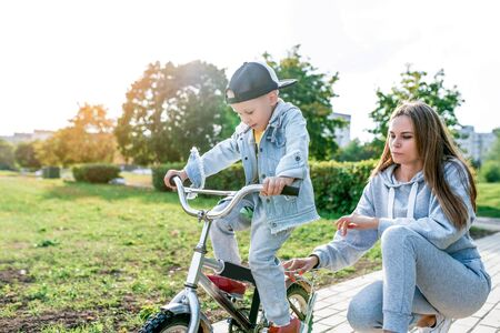 Young family, little boy 3-5 years old, mother woman, learn to ride bike, in summer in city park. Weekend rest on sports field. Casual wear. Emotions love caring and parenting. Banco de Imagens