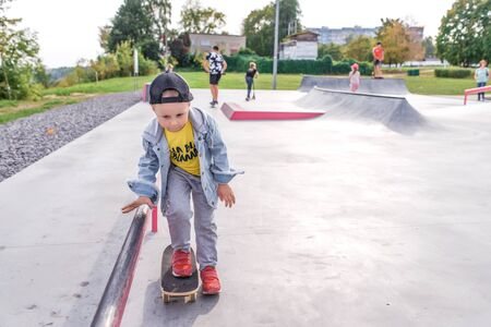 Little boy 3-5 years old, riding a skateboard, rest on weekend, education and training, the first steps on the board. In summer in city. Casual clothes, jeans. Free space for copy text.