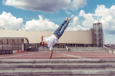 man standing on one arm, young guy dancer, summer city, dancing street dances, break of movement, modern youth style. Fashion fitness sport. Free space for copy text. Step cloud background