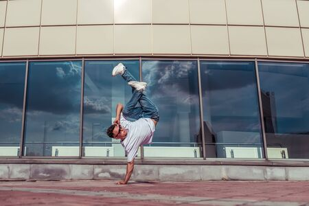 man in jump stands on one arm, dancer young guy, in summer in city, dancing street dances, modern style youth. Fashion and fitness sport. Free space for copy text. Glass window clouds background. Stock Photo