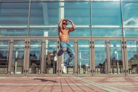 Jumping man, muscular torso, young guy dancer, in summer in city, dancing street dances, modern youth style. Fashion and fitness sport. Free space for copy text. Background glass doors.