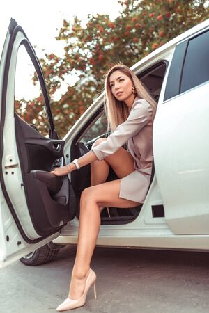 Woman gets out of car, summer in city, white business class car. Car rental, stylish and fashionable girl in high heels. Long hair tanned figure. VIP taxi, car sharing. Stock fotó