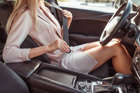 woman in pink jacket fastens her seat belt in summer in passenger compartment. Automatic gearbox, steering wheel and armrest. Tanned figure. Safety movement, activation of airbags Stock Photo